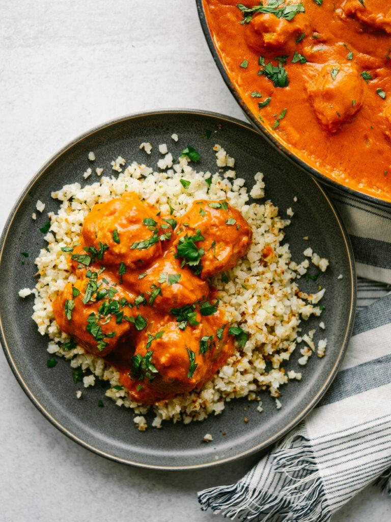 chicken tikka recipe on a plate with cauliflower rice