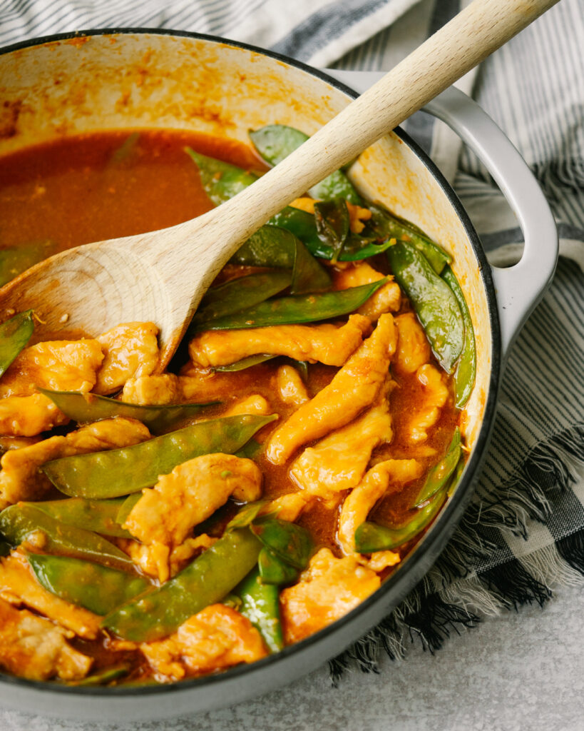 Three quarter view of sweet and sour pork chops with snow peas in a serving pan
