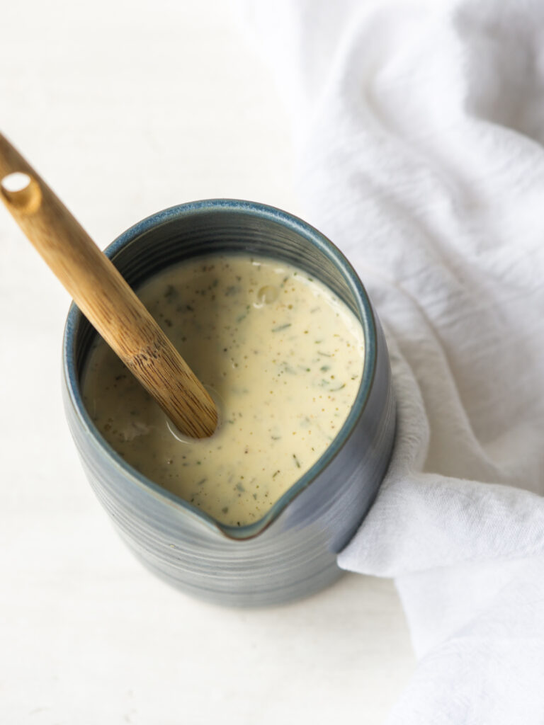 Above view of homemade dairy free ranch dressing in a ceramic pitcher