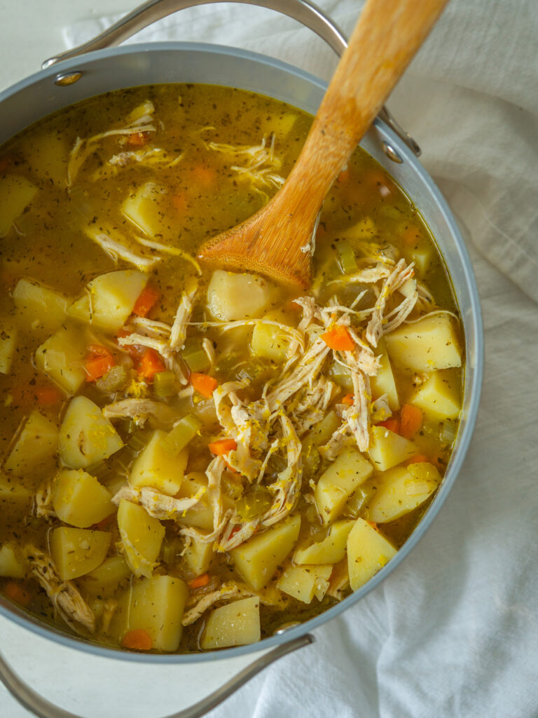 Above view of lemon chicken soup with potatoes in a large stock pot