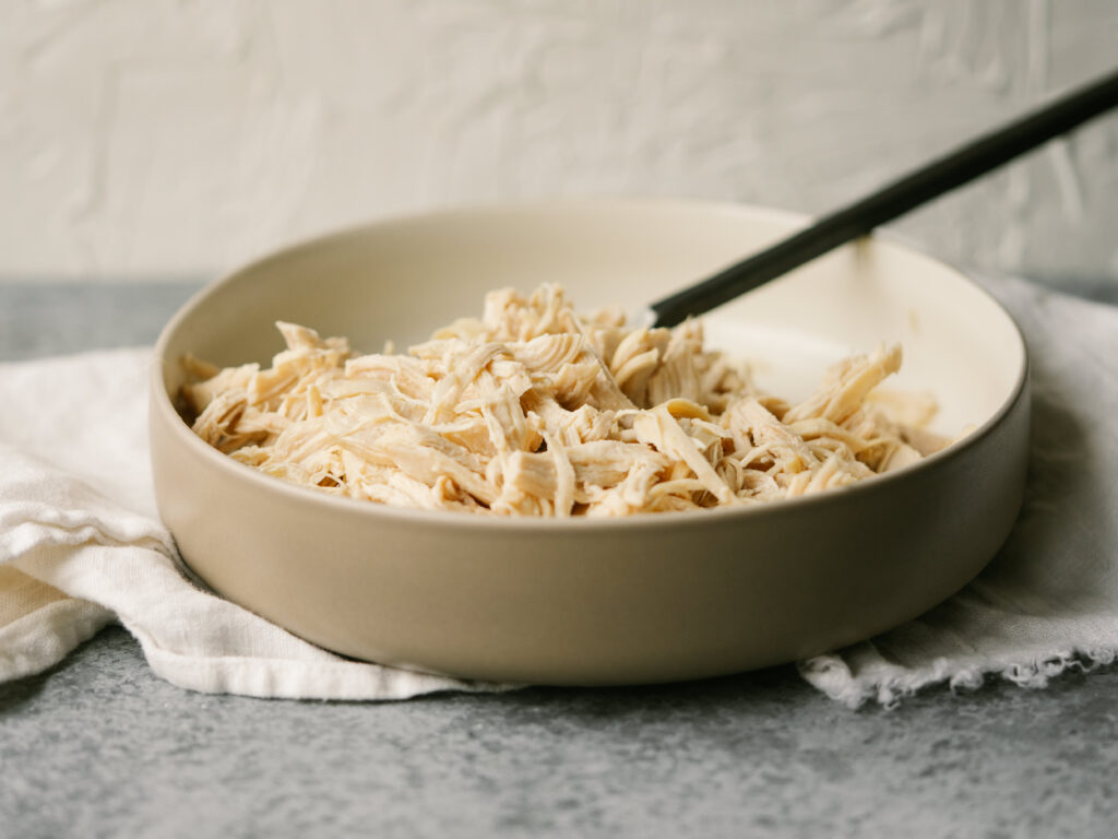 three quarter view of a bowl of instant pot shredded chicken