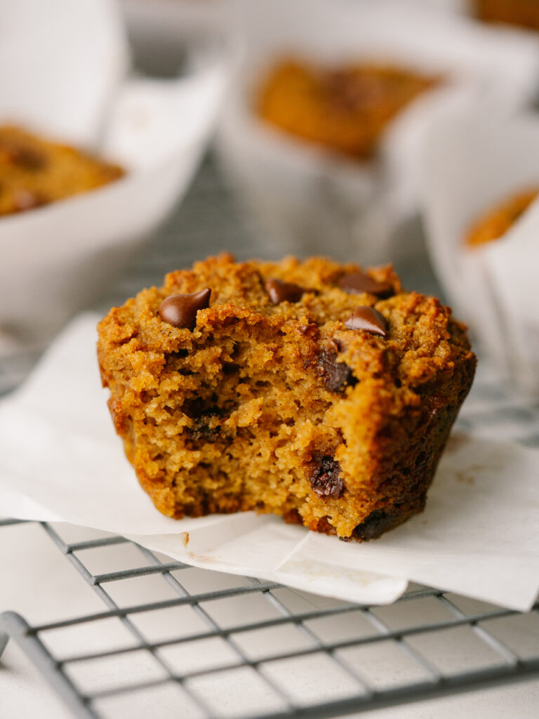 Side view of  a pumpkin chocolate chip muffin on a cooling rack