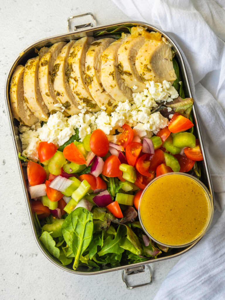 Above view of a salad in a lunch container with a small salad dressing container inside