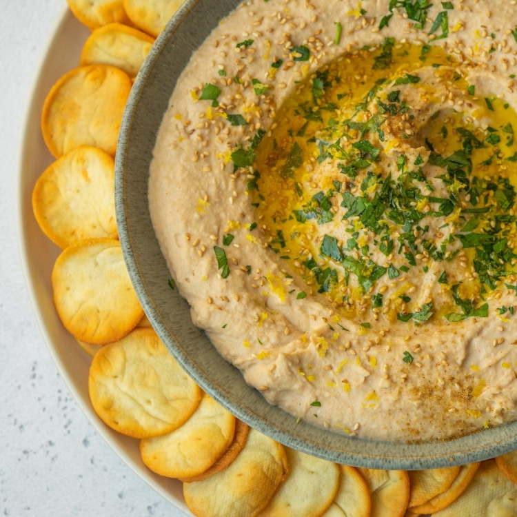Above view of creamy white bean hummus in a bowl served with pita crackers