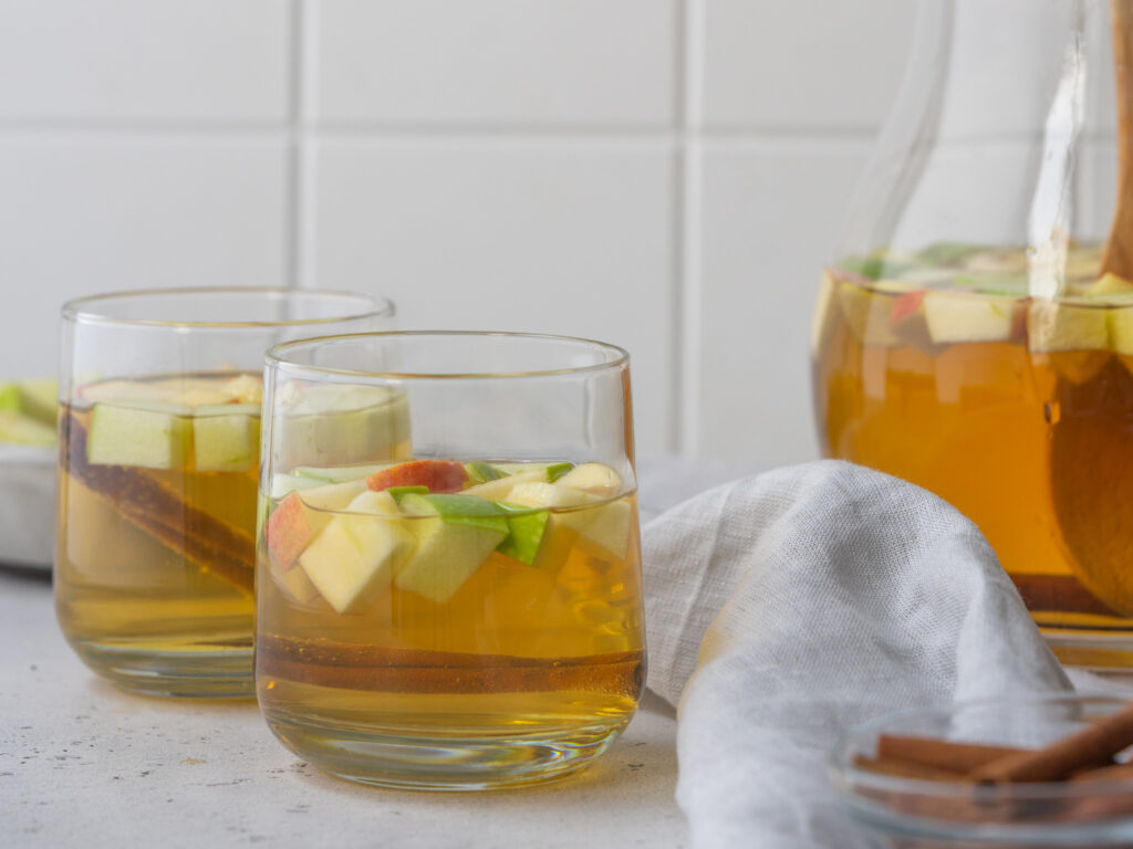 Side view of apple cider sangria in cocktail glasses with apple pieces and cinnamon sticks