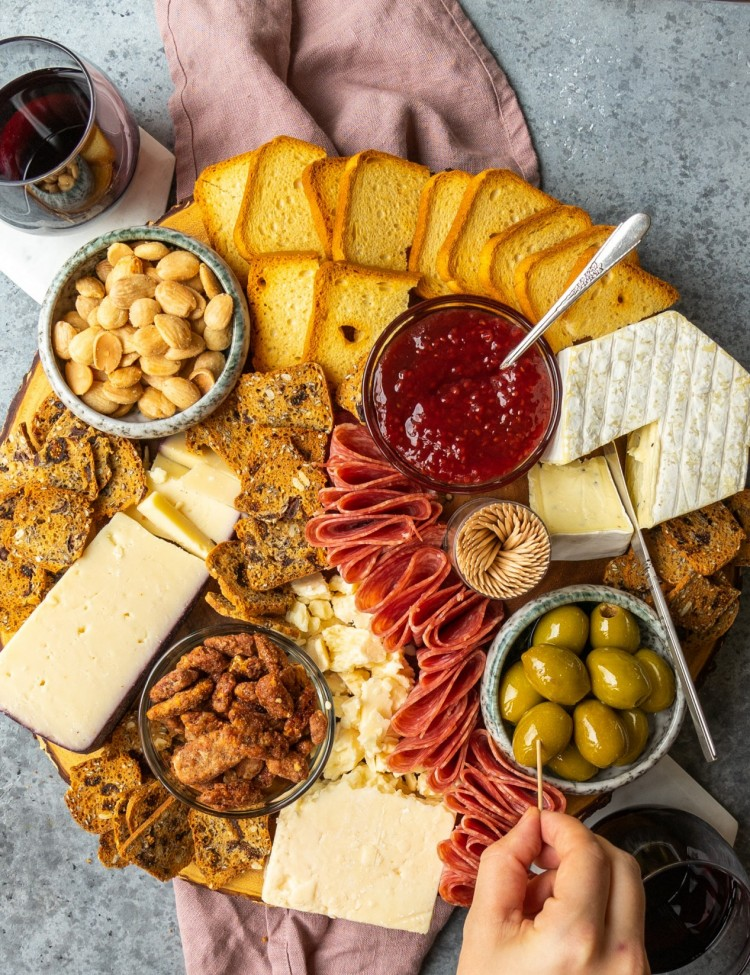 Above view of Trader Joe's holiday cheese board with a hand grabbing an olive