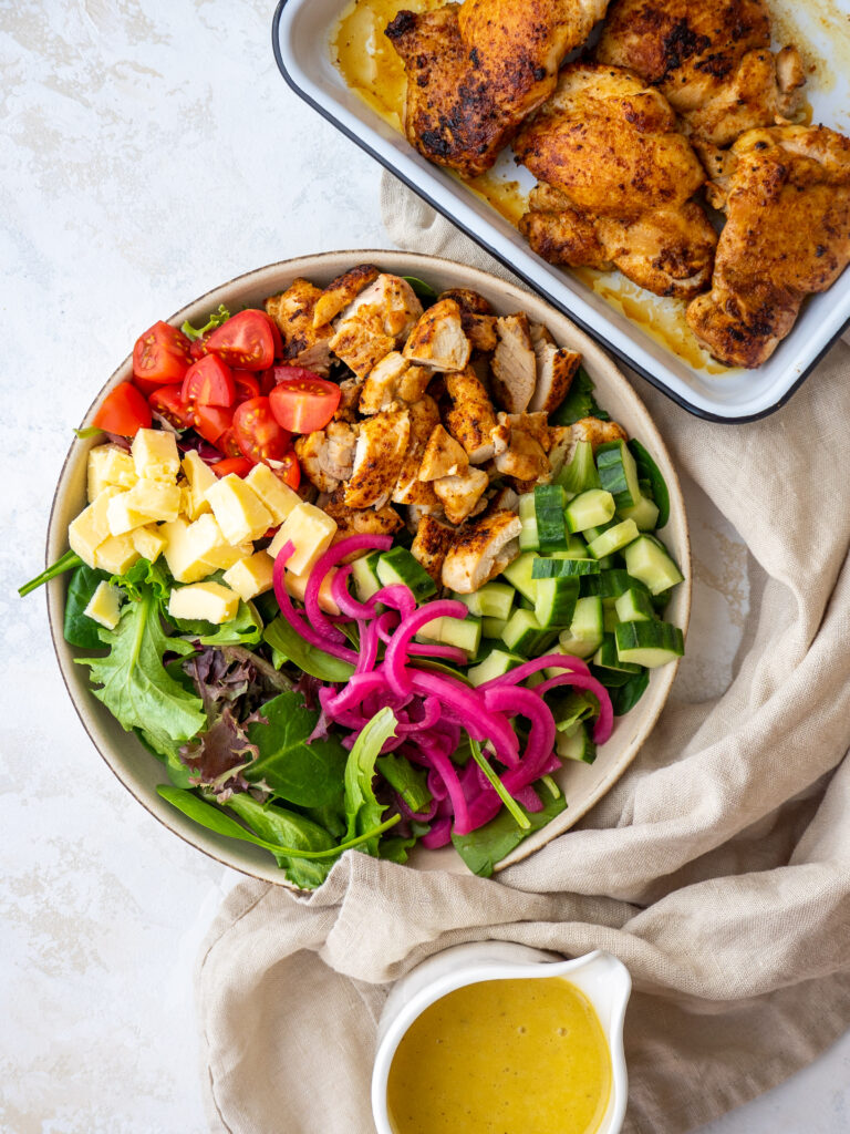 Above view of a salad with sliced pan fried chicken thighs on top