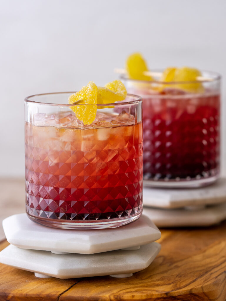 side view of cranberry Kentucky mule drinks in whisky glasses with a cadied ginger garnish