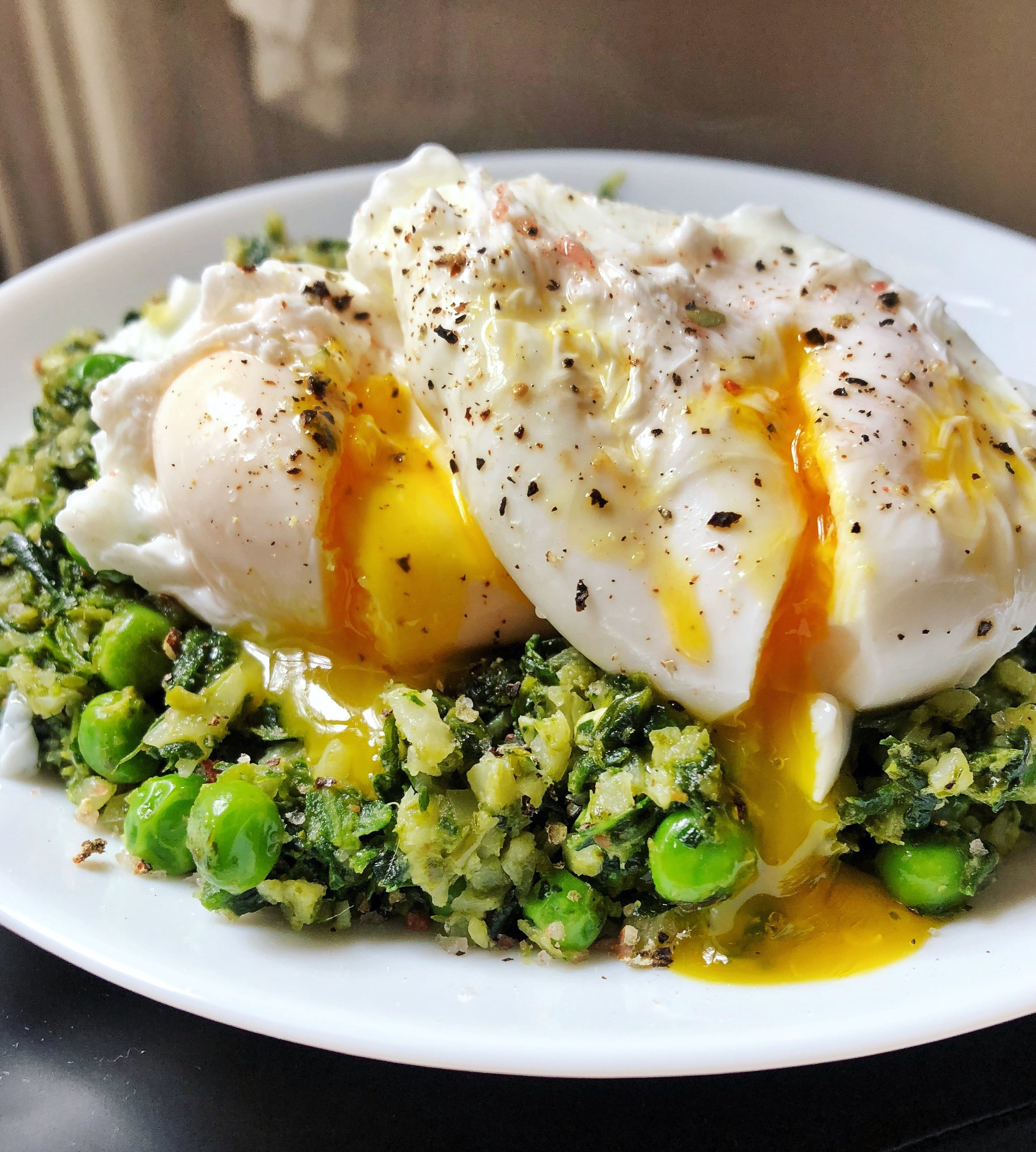 Side view of perfectly cooked poached eggs on cauliflower rice and veggies