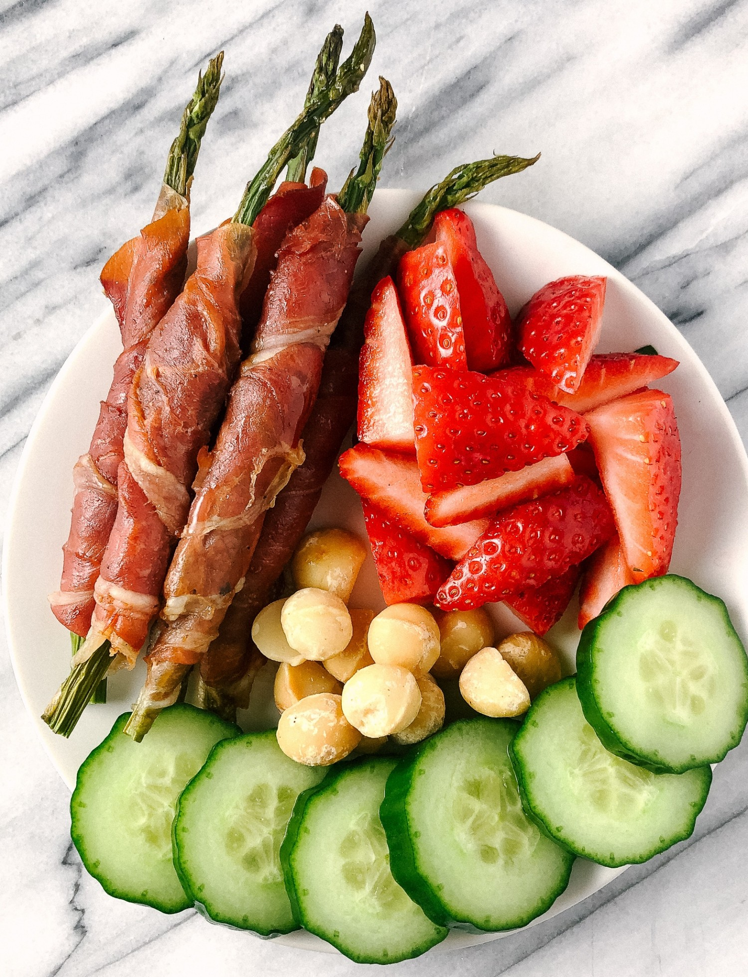 Above view of prosciutto wrapped asparagus on a snack plate with strawberries, macadamia nuts and sliced cucumbers