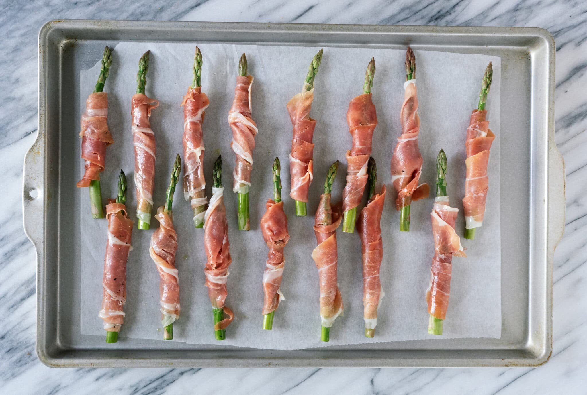 Above view of prosciutto wrapped asparagus on a baking sheet prior to being baked