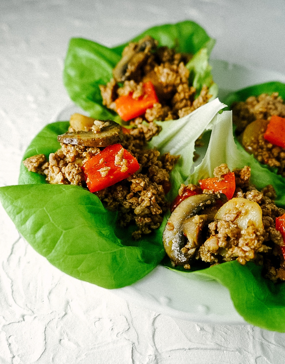 Three quarter view of pork lettuce wraps on a plate