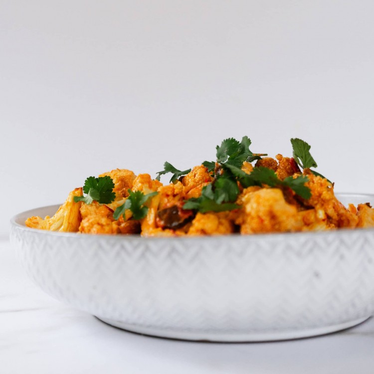 Side view of tahini and harissa roasted cauliflower in a bowl