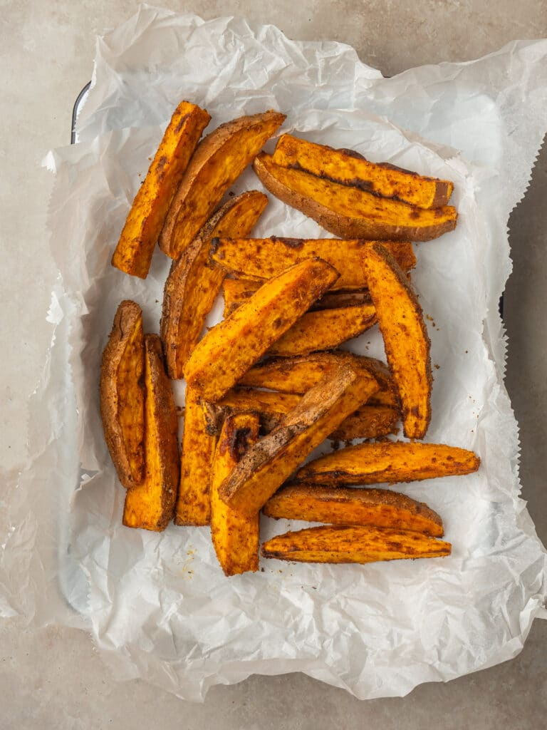Above view of seasoned sweet potato wedges made in the air fryer on a serving tray with parchment paper