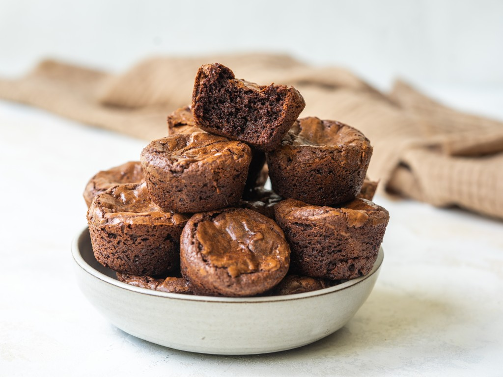 Side view of a stack of fudgy brownie bites on a serving plate with a bite out of one