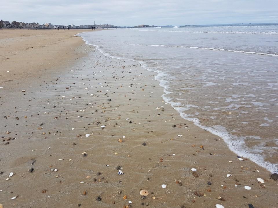 Madame Newstart - a propos - plage de Saint-Malo à marée basse, petits coquillages et galets sur le sable
