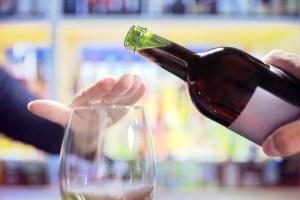 Femme refusant un verre de vin