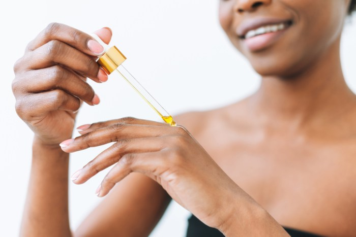 Beauty Portrait Of Smiling African Young Woman In Underwear With Cosmetic Oil For Hands And Body