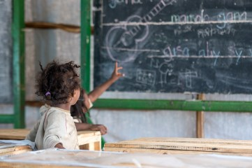 Two kids in a makeshift classroom
