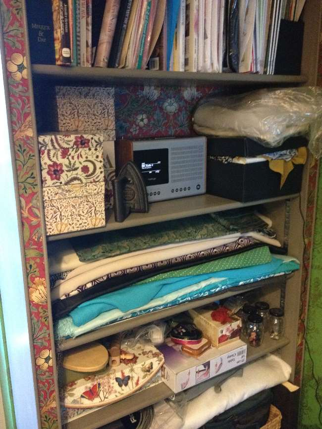 Shelving with fabrics, sewing books and radio