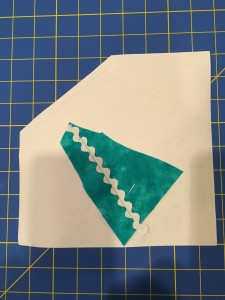 By holding the block up to a light source, I can pin the rickrack in place. I am looking at the block from the front, but sliding my rickrack in place from the back. Then pin in place, matching the edge of the rickrack with the wavy line on the pattern. Stitch the rickrack in place.