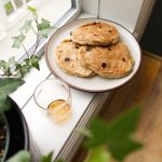 banana chocolate chip pancakes beside a glass of maple syrup by a window and a plant