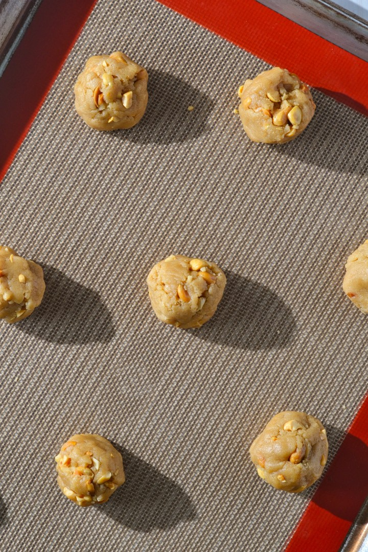 Raw peanut butter cookie dough balls on silicon lined baking sheet