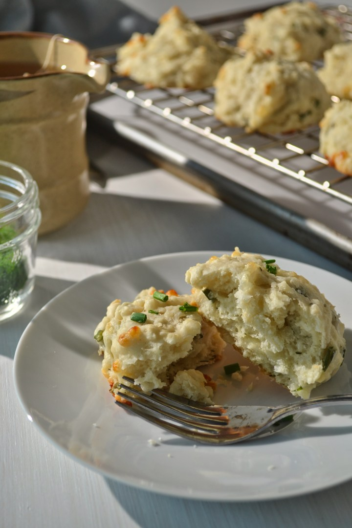 mozzarella herb drop biscuit on a white plate in front of a mug of tea