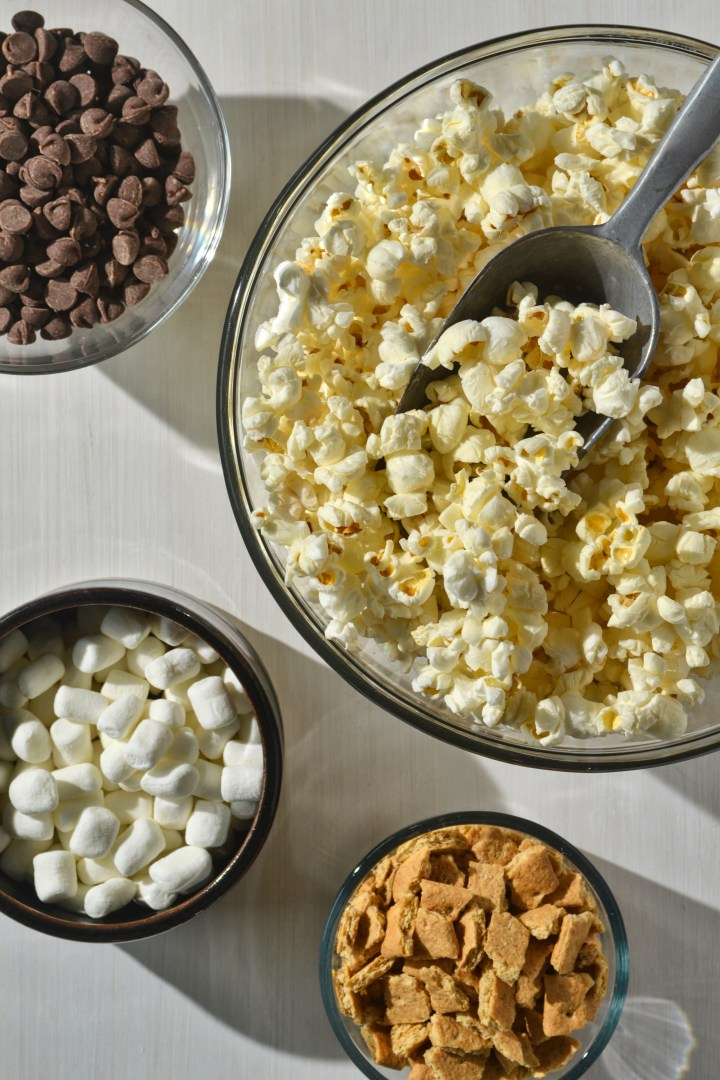 ingredients for easy s'mores popcorn mix (popcorn, chocolate chips, graham crackers, mini marshmallows) in separate bowls