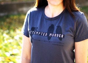 Elizabeth models an 'Attempted Murder' T-shirt - black printing on charcoal
