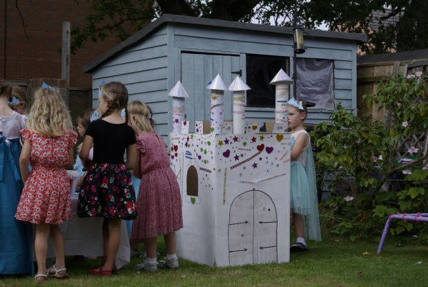 Girls decorating a cardboard castle at a Frozen garden party