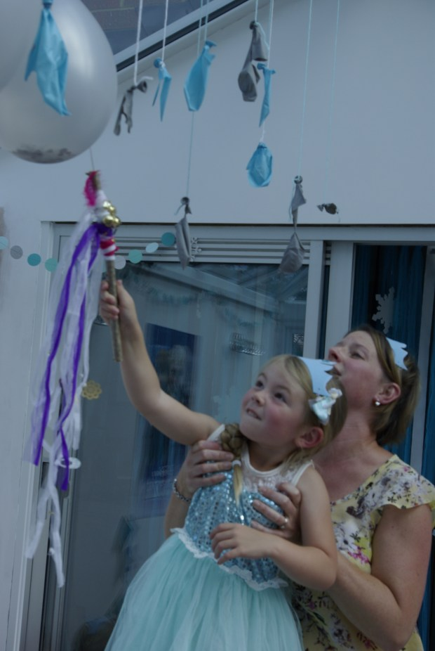Making it snow using Frozen themed party games.  Girl popping a balloon filled with snow.