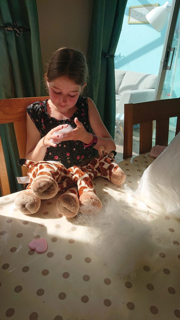 giraffe teddy being made by little girl