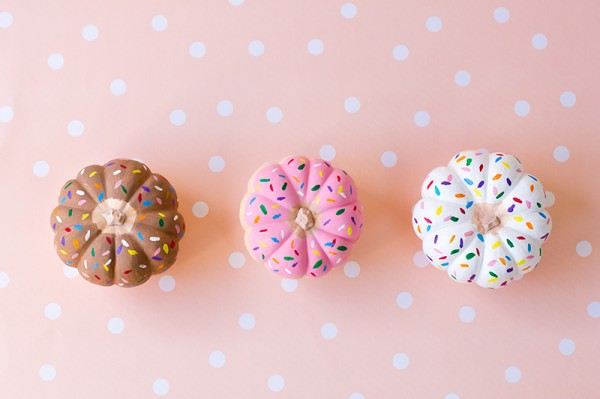 Mini pumpkins painted to look like doughnuts with sprinkles