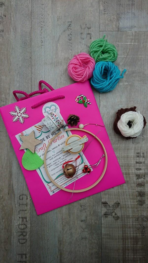 Paper party bag containing supplies to make a pom pom wreath