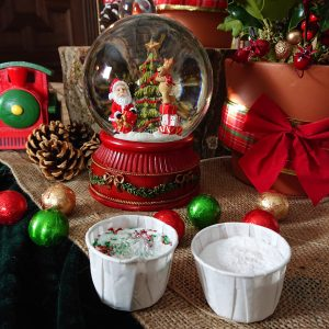 2 bath bombs with Christmas decorations in the background