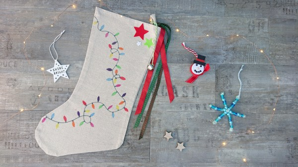 Christmas craft kit for children showing a fabric stocking to decorate, beaded snowflake and a light up snowman.