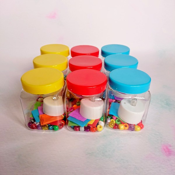 Colourful plastic pots filled with craft supplies