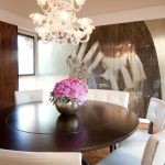 Amazing expandable round dining table Modern Dining Room in Baltimore with wood panel wall and white leather chairs