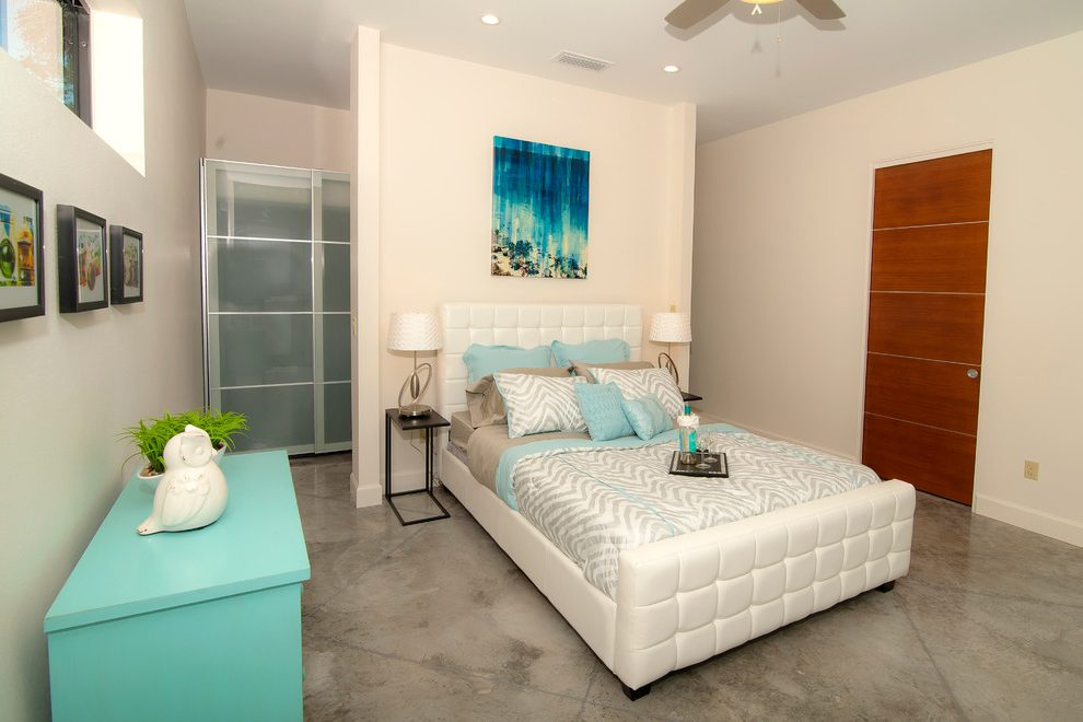 Dishy button tufted bed frame Contemporary Bedroom in Orlando with acid stained concrete floors and light blue bedding