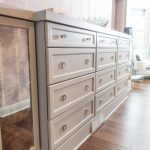 Magnificent bone inlay chest of drawers Transitional Bedroom in Cleveland with antique mirror and button tufted ottoman