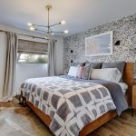 Marvelous silver cowhide rug in with light wood headboard and handdrawn wallpaper