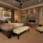 Pretty fireplace stacked stone Contemporary Bedroom in Philadelphia with dark wood bed and beige roman shade