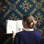 Pernille in front of a blue and gold wallpaper, standing with her back to the camera with an open book in hand.
