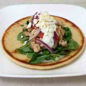 Greek chicken gyro topped with homemade Tzatziki sauce