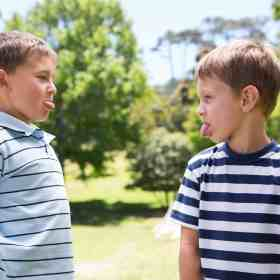 Two brothers engaged in a sticking out their tongue war. Discover our tips for how to end sibling rivalry for good. And for more parenting tips and kid inspiration, follow Made In A Pinch on Pinterest!