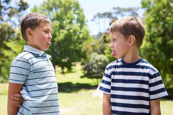 Two brothers engaged in a sticking out their tongue war. Discover 4 simple strategies to end sibling rivalry for good. And for more parenting tips and kid inspiration, follow Made In A Pinch on Pinterest!