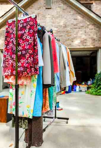 a hanging clothes rack in a driveway garage sale
