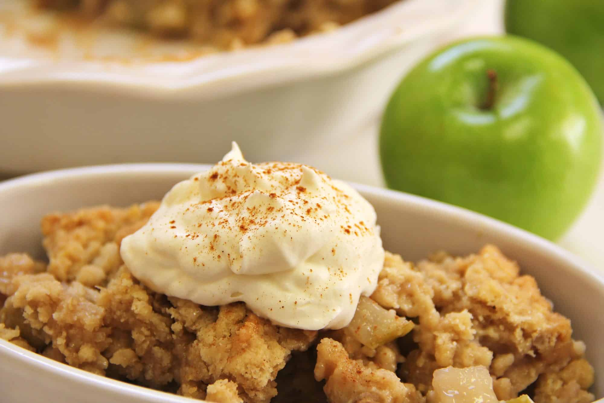A bowl with fruit crisp and a dollop of whipped cream