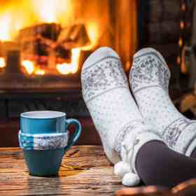 relaxing with a hot drink by the fire